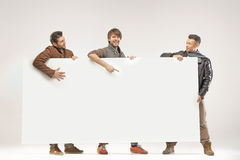 Young joyful guys holding white board Royalty Free Stock Photos
