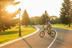 Young joyful man on bicycle outdoors. Handsome male tourist riding bicycle on country road, beautiful sunny day. Fitness, sport, people and healthy lifestyle Royalty Free Stock Photography