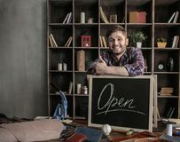 Young joyful man leather worker standing near open sign at wooden table Stock Image