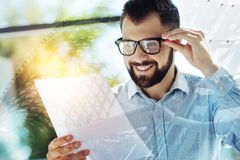 Young joyful man observing the document and smiling. Good results. Young bespectacled joyful man observing the document and holding hand near head and smiling Stock Images