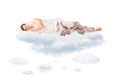 Young joyful man sleeping on a cloud. Young joyful man in pajamas sleeping on a cloud and dreaming isolated on white background Stock Photo