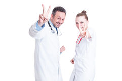 Young joyful medical coworkers gesturing victory Stock Photos