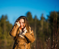 Young joyful nice blond woman clothed sheepskin coat and scarf.  Girl is enjoying a warm sunny spring day and her long Royalty Free Stock Image