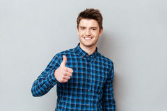Young joyful student man holding thumb up. Young joyful student man wearing casual holding thumb up over grey stock images