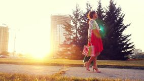 Young joyful woman in beautiful dress with shopping bags goes on the street through the sun during sunset in slowmotion stock video footage