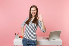 Young joyful woman in casual clothes showing OK sign work, standing near white desk with laptop isolated on pastel pink. Background. Achievement business career royalty free stock photography
