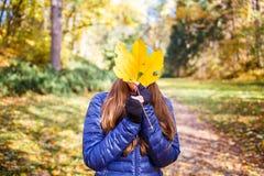 Young joyful woman in fall park. Young joyful woman hiding her face behind big yellow leaf walking at autumn park Stock Image