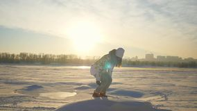 Young joyful woman jumps up on the mountain top in winter sunny day at sunset with lense flare effects in slow motion on. Young joyful woman jumps up on the stock video