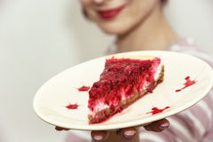Young joyful woman with the piece of cheesecake with raspberries Royalty Free Stock Images