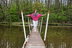 Young joyful woman is posing on the bridge with the forest behin Royalty Free Stock Image