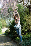 Young joyful woman posing under flowering tree. Spring is back Royalty Free Stock Photos