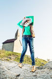Young joyful woman with stylish hat and an old romanesque church Royalty Free Stock Image