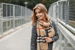 Young joyful woman with a sweet smile in a trendy coat with a trendy checkered scarf walks down the street. Near a vintage metal fence. Positive girl has fun stock images
