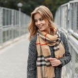 Young joyful woman with a sweet smile in a trendy coat with a trendy checkered scarf walks down the street. Near a vintage metal fence. Positive girl has fun royalty free stock images