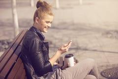 Young joyful woman texting on a fresh air Royalty Free Stock Photos