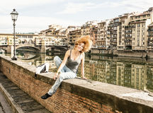 Young joyful woman tossing her hair on the wall in front of the Royalty Free Stock Photo