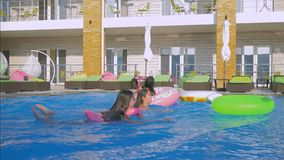 Young joyful women friends with long hair and slender bodies are actively having fun at pool jumping into water with