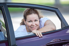 Young joyous beauty woman looking at opened car window Royalty Free Stock Photography