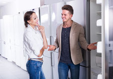 Young joyous couple choosing new refrigerator in hypermarket Royalty Free Stock Photo