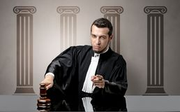 Young judge making decision. Young judge in front of a courthouse symbol making decision Stock Image