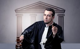 Young judge making decision. Young judge in front of a courthouse symbol making decision Stock Photos