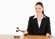 Young judge knocking a gavel smiling at the camera royalty free stock photography