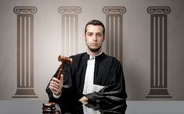 Young judge making decision. Young judge in front of a courthouse symbol making decision Royalty Free Stock Images