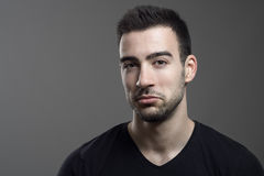 Young judging assertive man with not bad expression looking at camera Royalty Free Stock Images