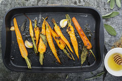 Young juicy carrots baked with honey, sage, garlic, olive oil, salt for a homely comfortable dinner on the background. Top View stock image