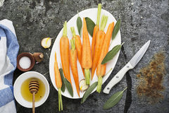 Young juicy carrots baked with honey, sage, garlic, olive oil, salt for a homely comfortable dinner on the background. Top View stock images
