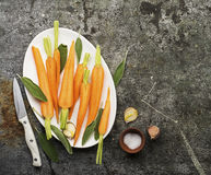 Young juicy carrots baked with honey, sage, garlic, olive oil, salt for a homely comfortable dinner on the background. Top View royalty free stock image