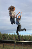 Young Jumpers. Two preteen kids playing and jumping on a trampoline Royalty Free Stock Images
