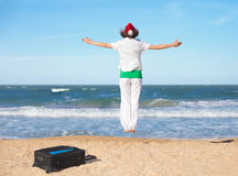 Young jumping on the beach. Young happy girl wearing Santa's hat jumping on the beach royalty free stock image
