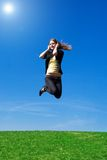 The young jumping girl with headphones Stock Photos