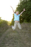 Young jumping girl portrait. Young jumping schoolgirl portrait over blurred leafs background Stock Image