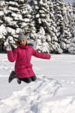 Young jumping girl in snowy winter outdoors Stock Photography