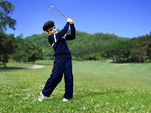 Young Junior golfer swing. Ing the ball on a golf course Royalty Free Stock Photos