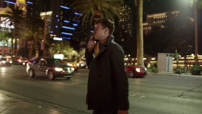 Young just arrived tourist is talking over his smartphone while walking on a sidewalk. Young tourist is talking over his smartphone while walking on a sidewalk stock footage