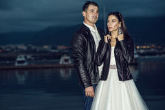 Young just married beautiful stylish couple in black leather jackets standing on the berth in the bay at dusk Royalty Free Stock Photos