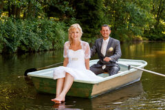 Young just married bride and groom on boat. Beautiful young wedding couple, blonde bride with flower and her groom just married on small boat at pond with Royalty Free Stock Photo