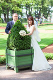 Young just married couple embracing green flowerbed Stock Photos