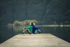 Free Young Just Married Couple Is Sitting On Pier By The Volcanic Lake. Royalty Free Stock Image - 138334306