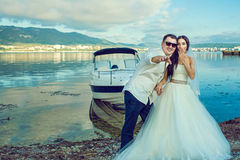 Young just married couple standing near the boat at the seaside in wedding dress and suit. Royalty Free Stock Image