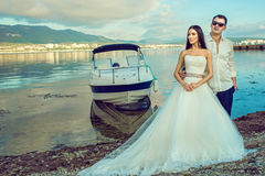 Young just married couple in wedding gown and suit standing near the boat at the seaside looking aside royalty free stock image