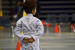 Young karate boy waiting. Young white belt karate boy waiting for his time for tournament with orange cones, bleachers, yellow banner and chair in the background Stock Photos