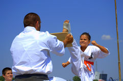 Young karate girl breaking a board Stock Photos