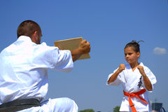 Young karate girl concentrating for breaking a board Royalty Free Stock Photography