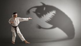 Karate man fighting with a big scary shadow Stock Image