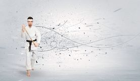 Karate man doing karate tricks with chaotic concept. Young karate trainer doing karate tricks with chaotic concept stock photography
