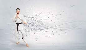 Karate man doing karate tricks with chaotic concept. Young karate trainer doing karate tricks with chaotic concept stock images